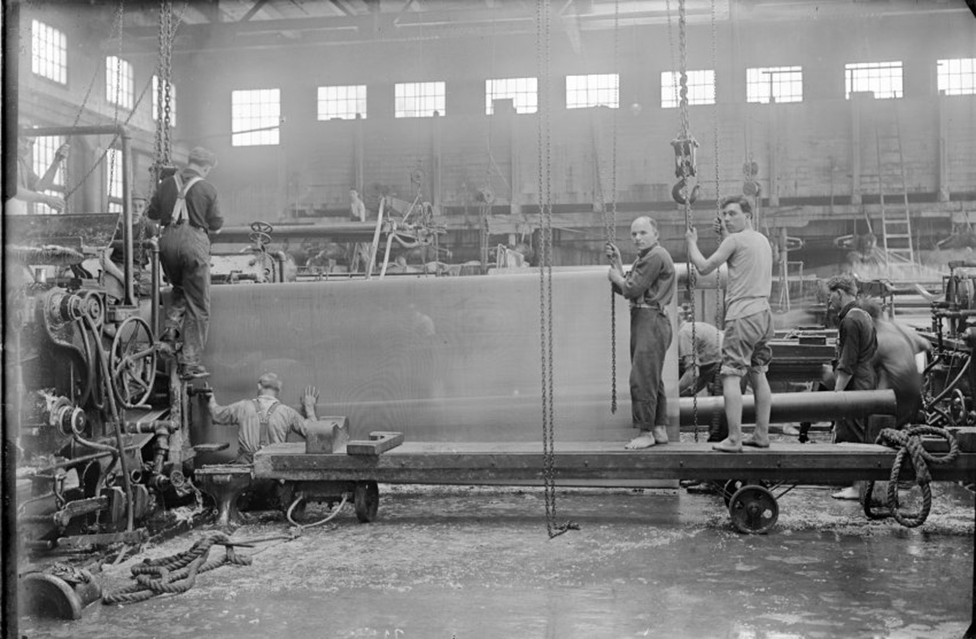 Machine Room #1 with crew at the Powell River Company changing wire screen on a paper machine, 1916.