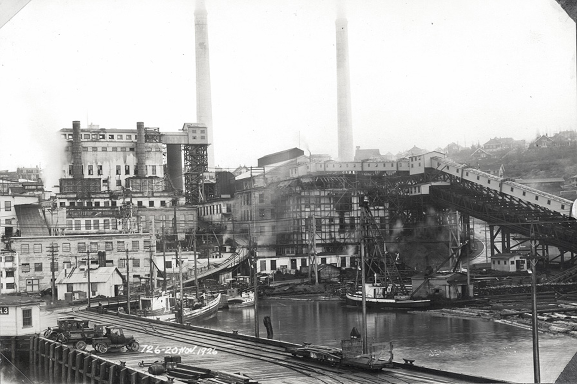 View of the Powell River Company Mill, 1926. Model T Ford wagons are parked on the wharf.